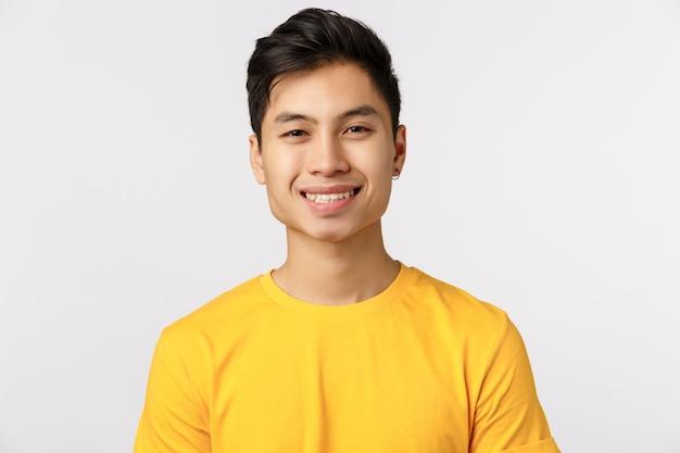 Uomo asiatico sveglio nel sorridere giallo della maglietta