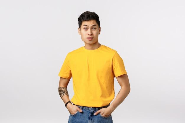 Uomo asiatico sveglio nella posa gialla della maglietta