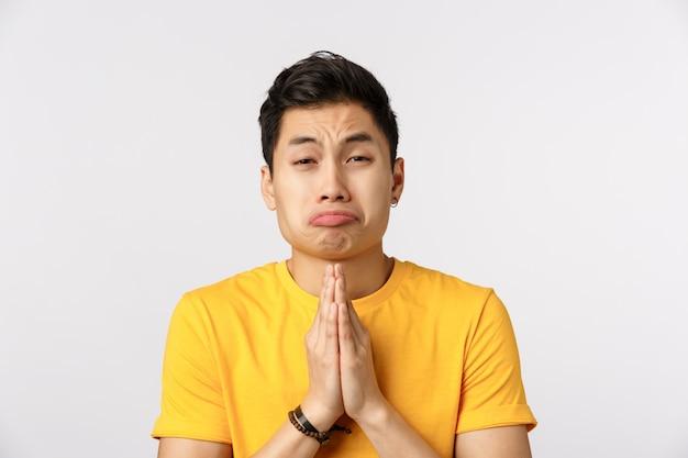 Uomo asiatico sveglio nella preghiera gialla della maglietta
