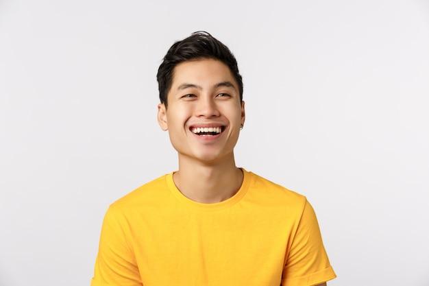 Uomo asiatico sveglio nella risata gialla della maglietta