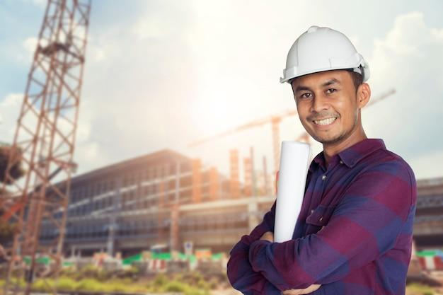 Uomo asiatico tailandese, ingegnere che indossa casco bianco e in possesso di stampa blu in piedi con grande sm