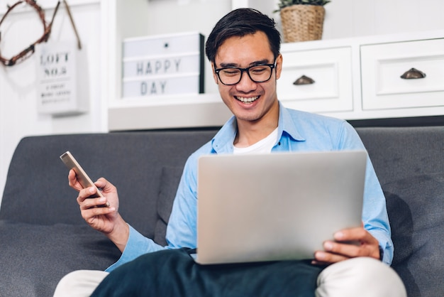 Uomo asiatico utilizzando laptop a casa