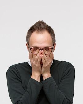 Uomo assonnato in occhiali stropicciandosi gli occhi, si sente stanco dopo aver lavorato sul computer portatile. superlavoro, occhiali sfocati, affaticamento cronico, stress mentale, mancanza di sonno