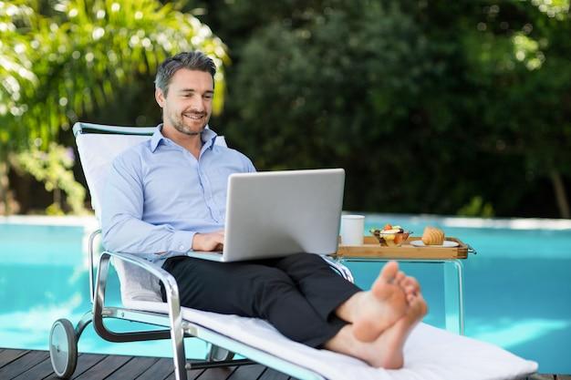 Uomo astuto che per mezzo del computer portatile vicino allo stagno