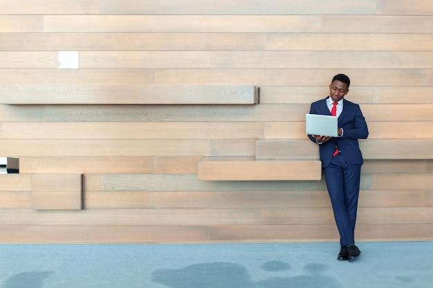 Uomo astuto di affari africani che utilizza computer portatile nell'ufficio con copyspace