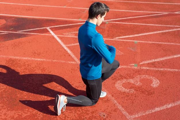 Uomo atleta sulla linea di partenza di una pista da corsa allo stadio, appoggiato sulle sue ginocchia.