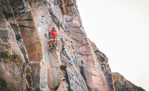 Uomo atletico che arrampica una parete di roccia
