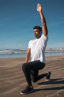 Uomo atletico che fa esercizio alla spiaggia.