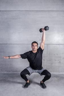 Uomo atletico che fa esercizio di dumbbell