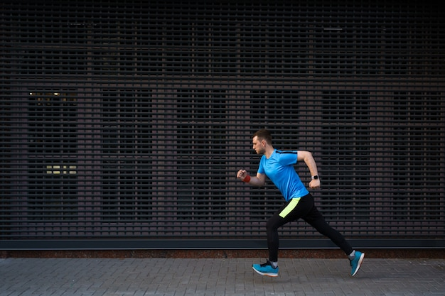 Uomo atletico che funziona alla via urbana su sfondo grigio