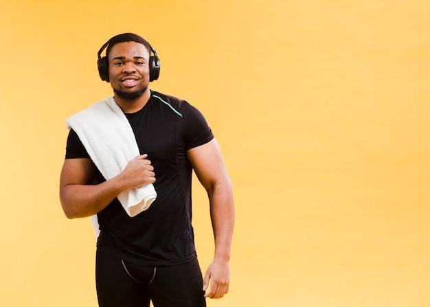 Uomo atletico che posa in attrezzatura e asciugamano della palestra