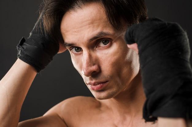 Uomo atletico che posa mentre indossando i guantoni da pugile