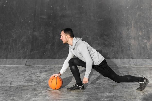 Uomo atletico che prepara correre con una palla