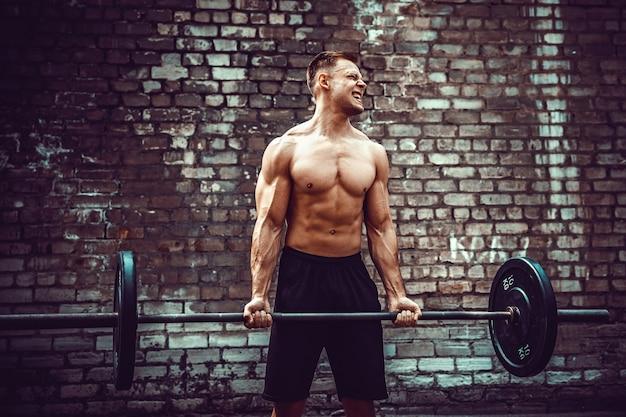 Uomo atletico che risolve con un bilanciere. forza e motivazione. esercizio bicipiti.