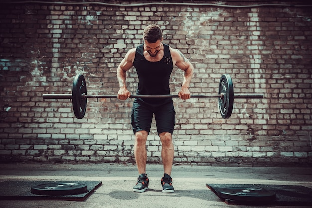 Uomo atletico che risolve con un bilanciere. forza e motivazione. esercizio per i muscoli della schiena