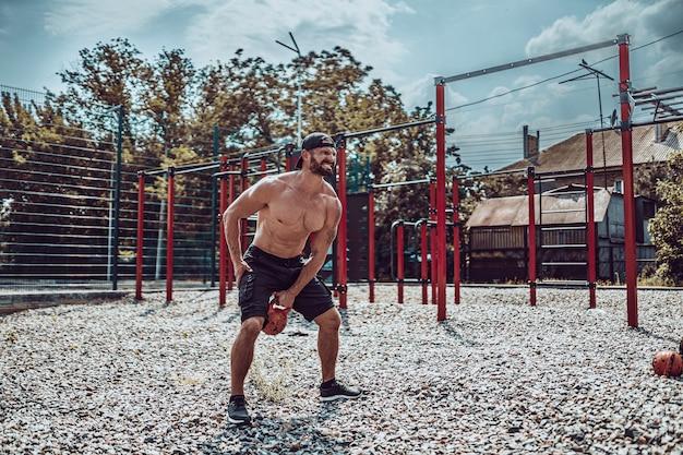 Uomo atletico che risolve con un kettlebell all'iarda della palestra della via