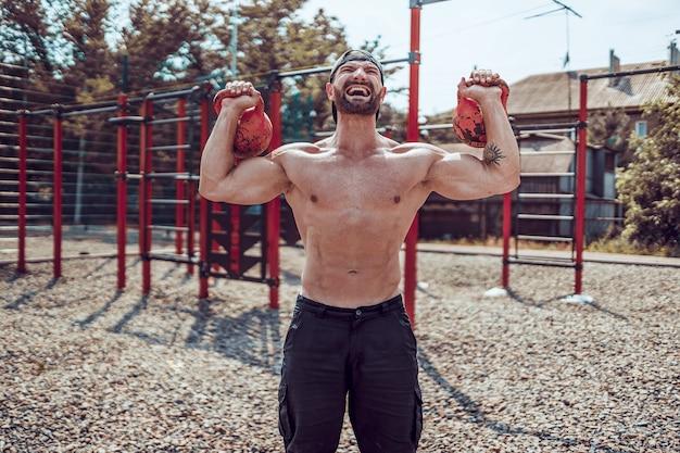 Uomo atletico che risolve con un kettlebell all'iarda della palestra della via.