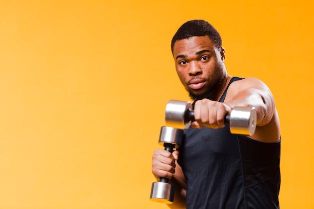 Uomo atletico che si esercita con i pesi e lo spazio della copia