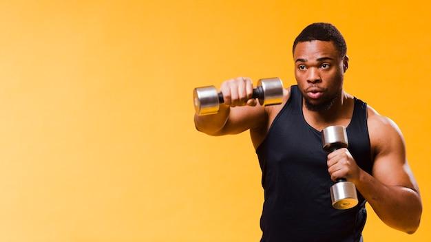 Uomo atletico che si esercita con i pesi