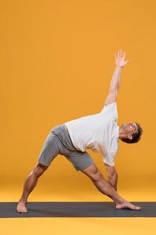 Uomo atletico che si esercita sulla stuoia di yoga