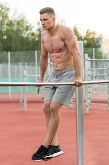 Uomo atletico che si prepara all'aperto senza camicia