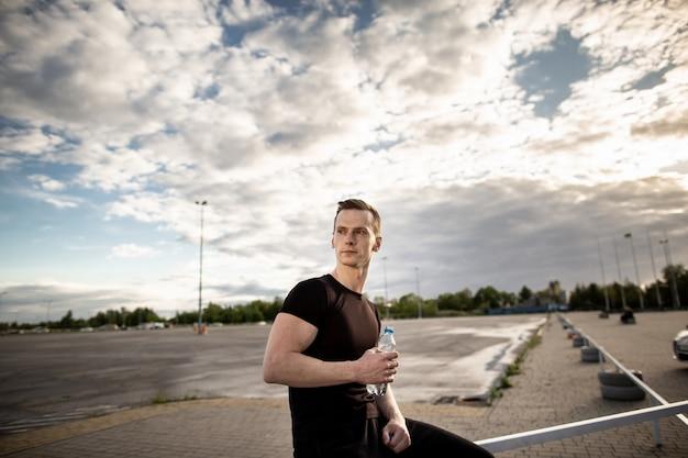 Uomo atletico che si siede sul recinto vicino al parco giochi e che tiene una bottiglia di acqua. l'uomo distoglie lo sguardo. pausa allenamento in una mattina di sole. stile di vita sano, concetto di sport