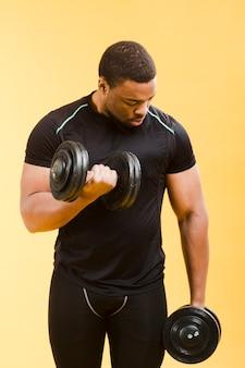Uomo atletico che tiene i pesi in attrezzatura della palestra