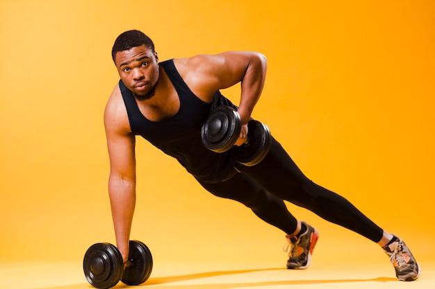 Uomo atletico che tiene i pesi mentre si esercita
