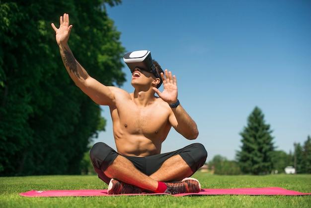 Uomo atletico che usando i vetri di una realtà virtuale all'aperto