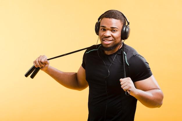 Uomo atletico con le cuffie e la corda di salto