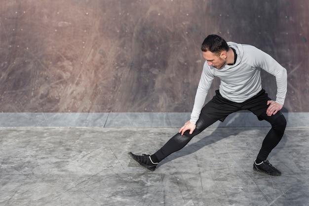 Uomo atletico di vista frontale che fa gli esercizi di riscaldamento