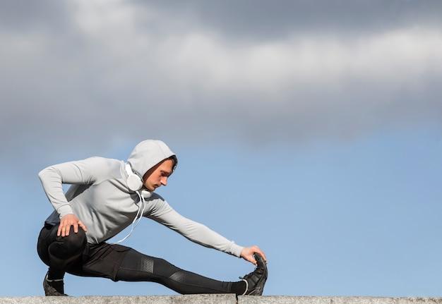 Uomo atletico di vista frontale che si scalda le gambe