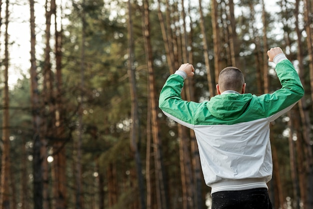 Uomo atletico di vista posteriore che risolve in natura