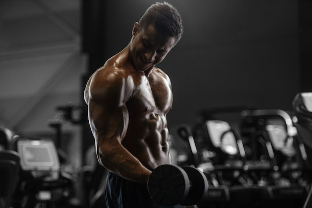 Uomo atletico forte bello che pompa i muscoli allenamento fitness e bodybuilding concetto sfondo - muscoloso bodybuilder fitness uomini facendo braccia addominali esercizi schiena in palestra torso nudo