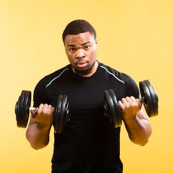 Uomo atletico forte che tiene pesi