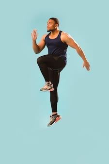 Uomo atletico nel salto dell'attrezzatura della palestra