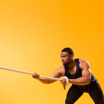 Uomo atletico nella corda di trazione dell'attrezzatura della palestra con lo spazio della copia