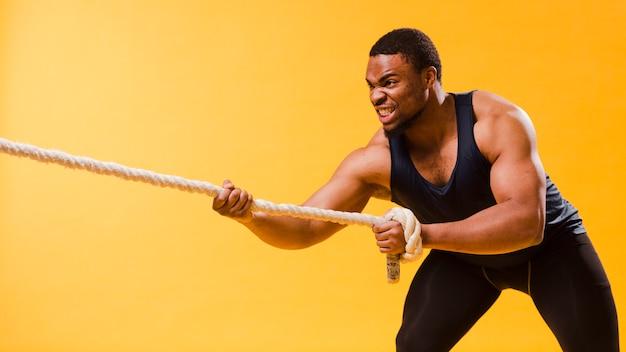 Uomo atletico nella corda di trazione dell'attrezzatura della palestra