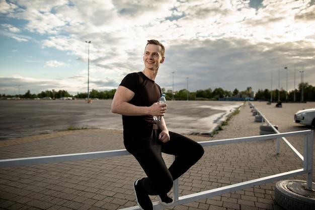 Uomo atletico seduto sul recinto vicino al parco giochi e sorridente, con in mano una bottiglia d'acqua. pausa allenamento in una mattina di sole. stile di vita sano, concetto di sport