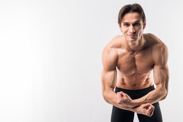Uomo atletico senza camicia che ostenta armi muscolose con lo spazio della copia