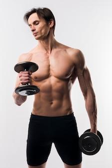 Uomo atletico senza camicia che risolve con i pesi