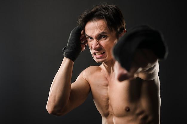 Uomo atletico senza camicia in guantoni da boxe