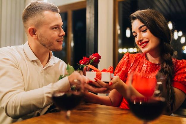 Uomo attento che dà i regali alla ragazza