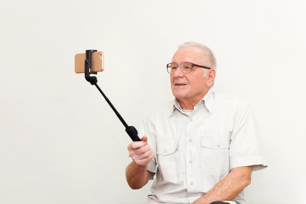 Uomo attivo anziano che prende selfie con il telefono cellulare isolato sul concetto grigio di blogger del vlog del fondo