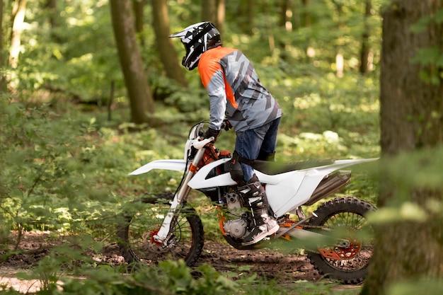 Uomo attivo che guida la motocicletta nella foresta