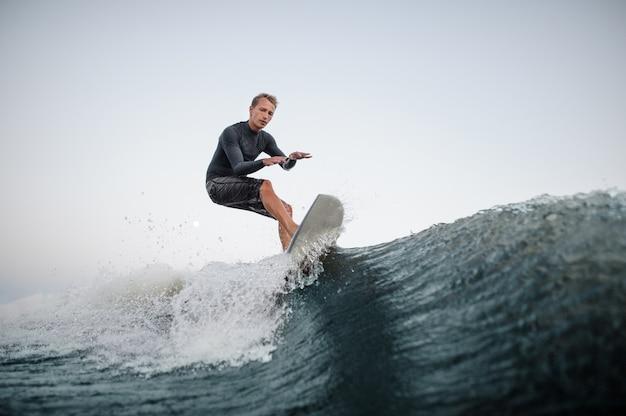 Uomo attivo che naviga sul bordo lungo l'onda blu