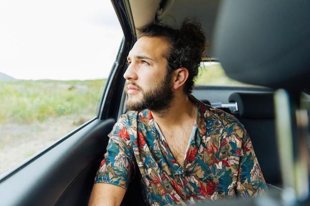 Uomo attraente che osserva in su il finestrino della macchina