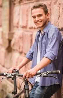 Uomo attraente che sta con la sua bicicletta vicino alla parete.