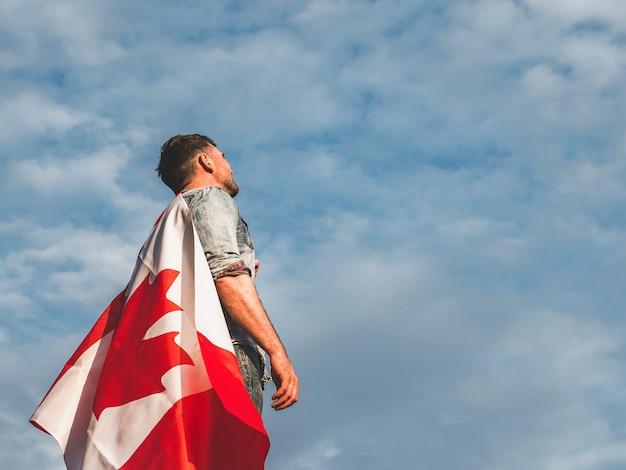 Uomo attraente che tiene bandiera canadese. festa nazionale
