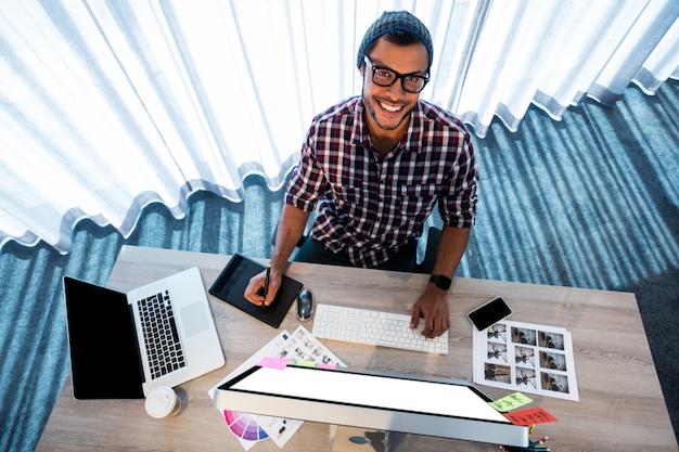 Uomo attraente dei pantaloni a vita bassa che sorride mentre lavorando allo scrittorio